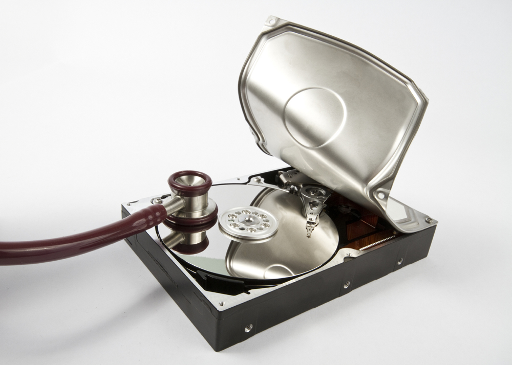 opened hard disk with stethoscope on grey background
